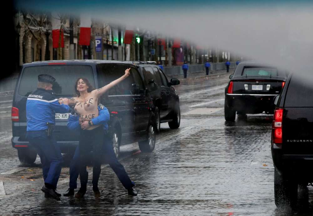 Topless female protester runs at Trump's motorcade in Paris