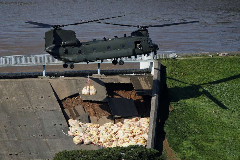 British military drop ballast sacks on dam to prevent flooding of UK town