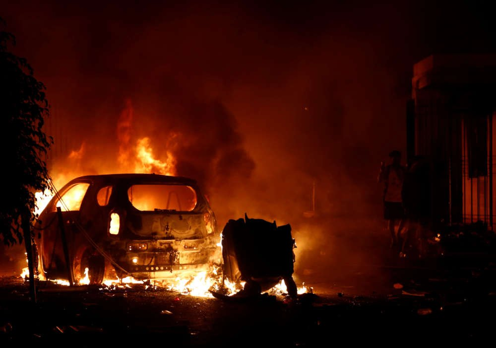 Rioting migrants torch cars