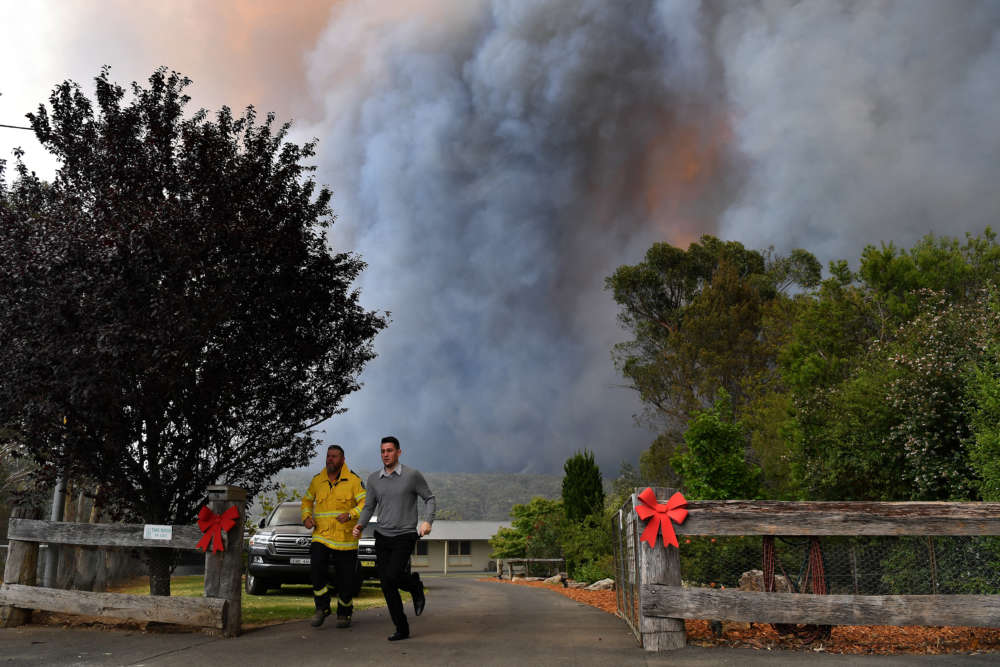 Australian PM apologises for vacation as firefighters killed in huge blazes