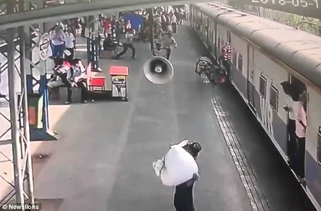 Hero policeman saves five-year-old girl's life after dragging her from under a train (Video)