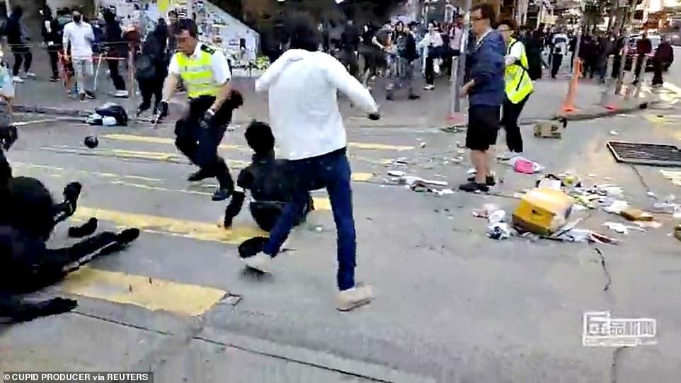 Hong Kong police officer shoots masked protester at point-blank range