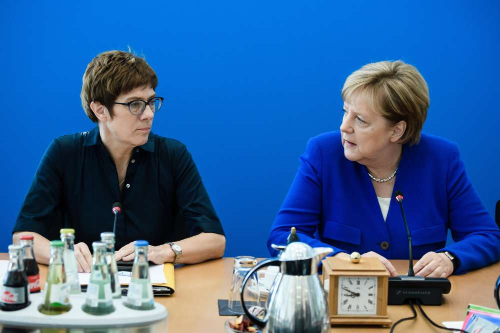 Merkel to fight another day after settling migration row
