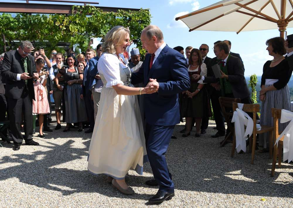 Cossacks and flowers as Putin dances at Austrian minister's wedding