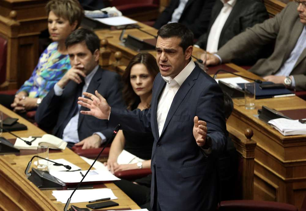 Greece passes fast-track reform package to unlock bailout cash