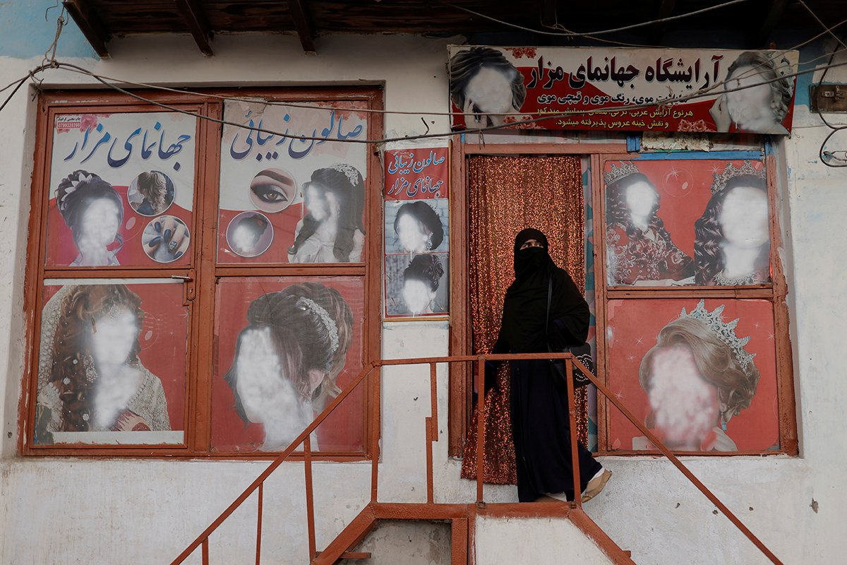 A Woman Wearing A Niqab Enters A Beauty Salon Where The Ads Of Women Have Been Defaced By A Shopkeeper In Kabul